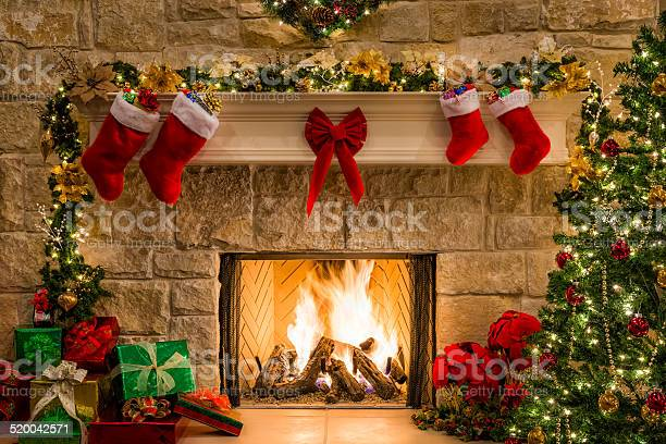 Photo of Christmas fireplace, tree, stockings, fire, hearth, lights, and decorations