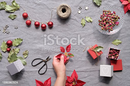 istock Christmas flat lay on natural beige linen textile. Hands decorate gift boxes. Red poinsettia, red baubles, winter decor. Dry rose tea leaves. Hemp cord, scissors, red and dark green poinsettia 1330362524