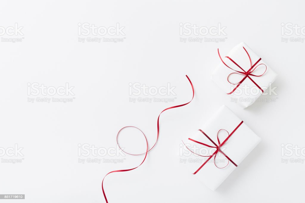 Christmas flat lay, white presents with red ribbon on white background