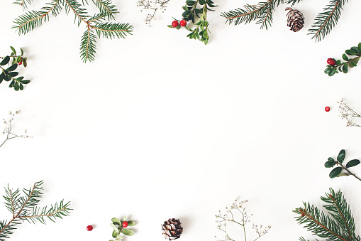 Christmas floral frame, decorative border. Winter composition of red cranberry branches, baby's breath flowers, spruce tree branches and larch cones on white table. Festive background. Flat lay, top view.