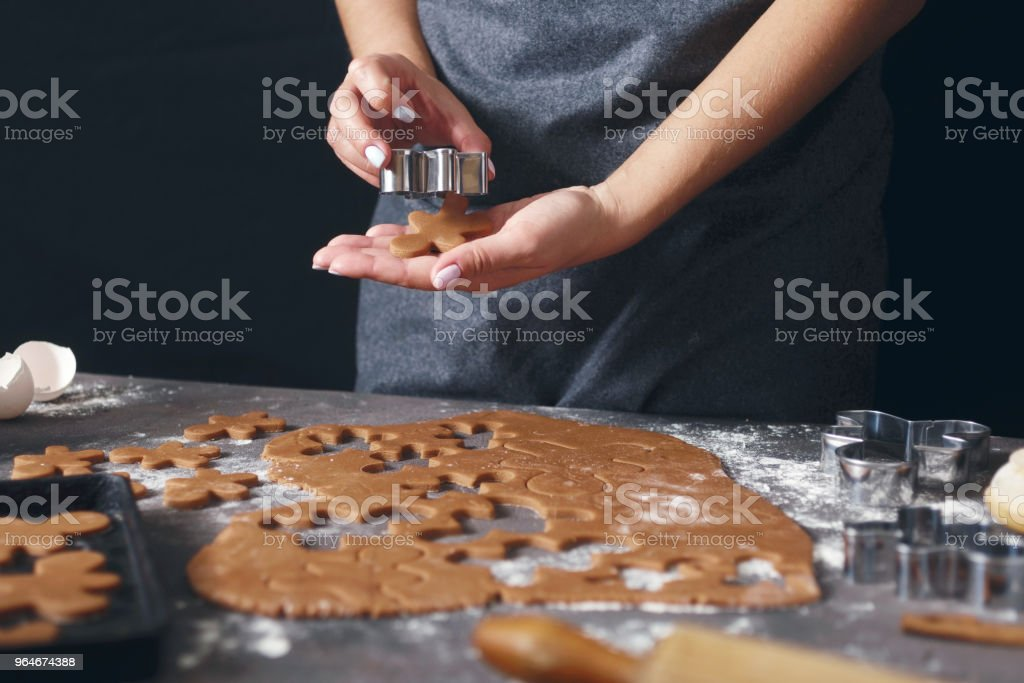 Christmas food concept. Woman is cooking gingerbread man cookies in Christmas. Xmas dessert royalty-free stock photo