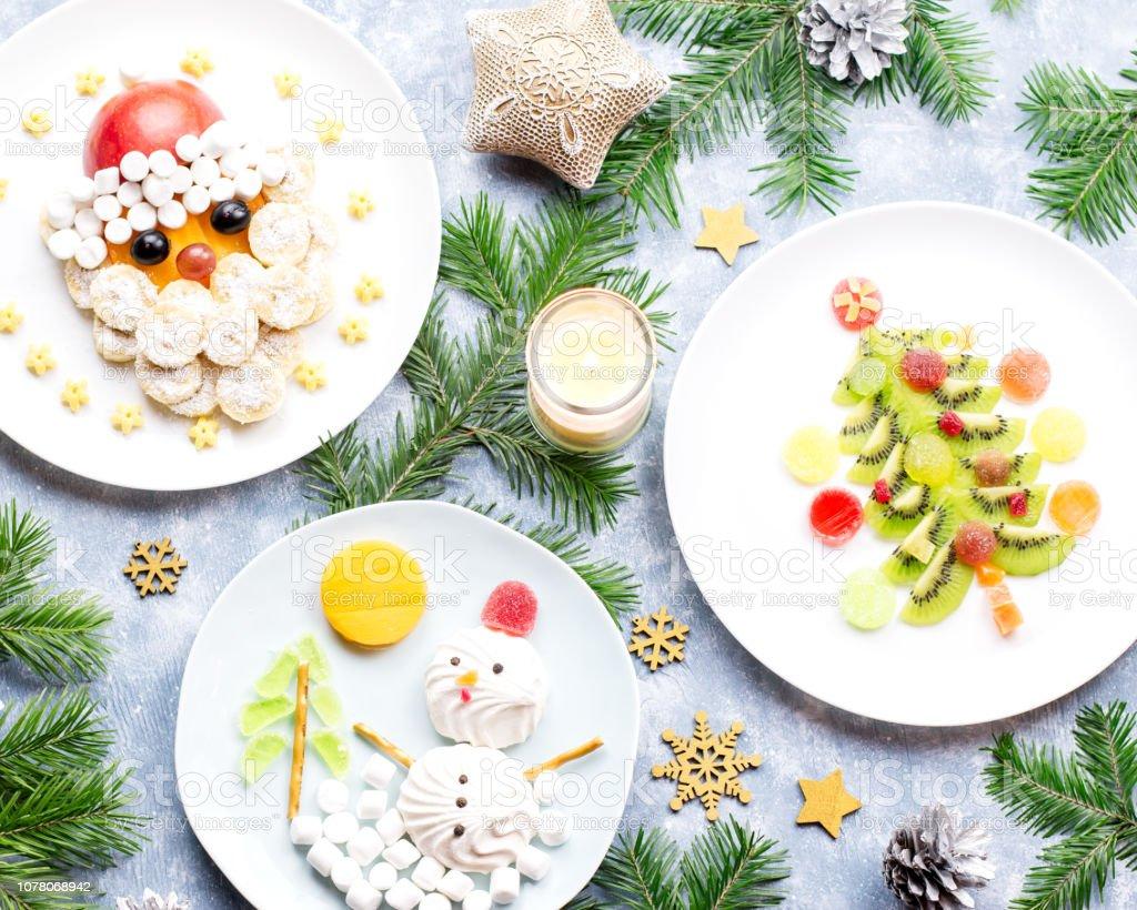 Christmas food for children - kiwi Christmas tree, marshmallow snowman, banana Santa Claus. Top view stock photo