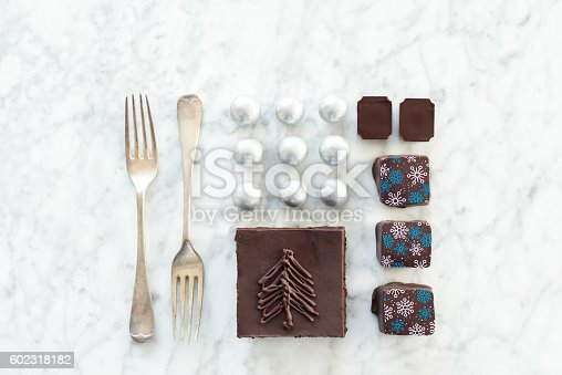 istock Christmas Food Knolling, Chocolates, Cake, Candies, Forks on Marble Background 602318182