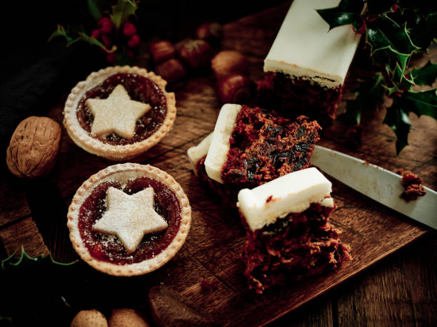 Christmas Food, Mince Pies, Christmas Cake, and mixed nuts with Holly on an aged dark wood surface.