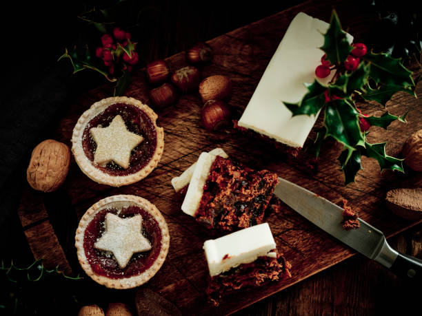 christmas food, mince pies, christmas cake, and mixed nuts with holly on an aged dark wood surface. - cake stock pictures, royalty-free photos & images
