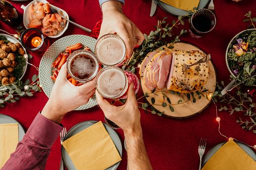 Christmas food smörgåsbord people toasting in beer  Photo taken from above overhead table top shot