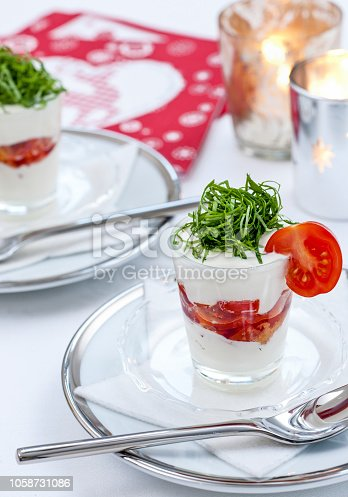 amuse bouche of parmesan cream with red pesto topped with basil and tomato on dining table with Christmas decoration