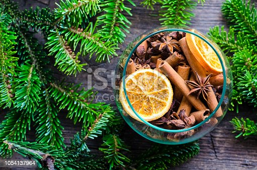 Christmas fragrance concept. Christmas spices still life with cinnamon sticks, star anise and dried orange slices in glass bowl on a wooden background with fir tree. Top view.