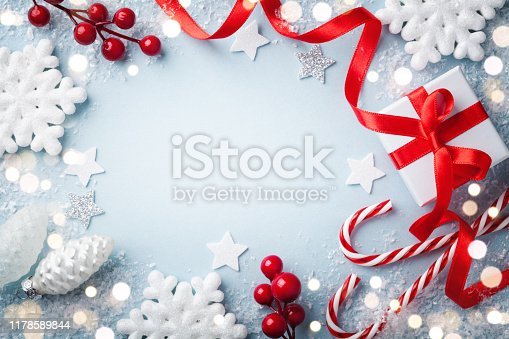Christmas frame, greeting card. Gift or present box and holiday decoration on blue background top view. Happy New Year composition with bokeh.