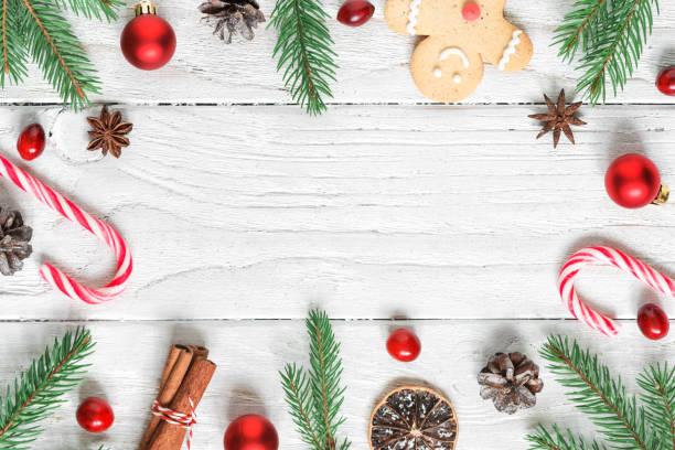 Marco de Navidad hecho de ramas de abeto, decoraciones, bayas, dulces, comida de navidad y conos de pino. plana lay - foto de stock