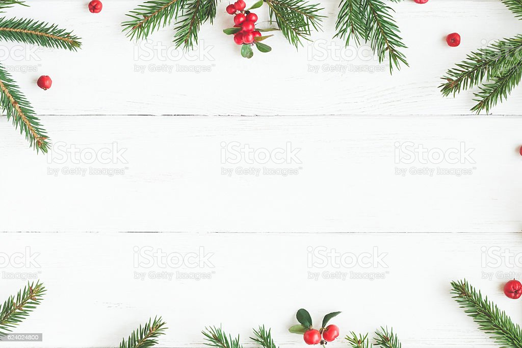 Christmas frame made of fir branches, red berries. Flat lay stock photo