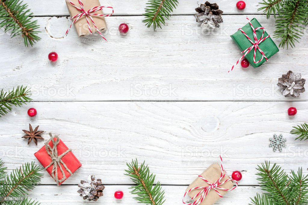 Christmas frame made of fir branches, red berries, gift boxes and pine cones stock photo