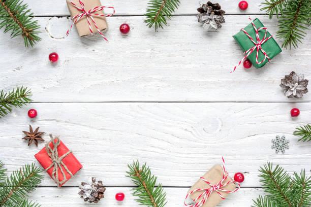 weihnachten-rahmen aus tannenzweigen, rote beeren, geschenkboxen und tannenzapfen - holzspielwaren stock-fotos und bilder