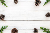 istock Christmas frame made of fir leaves and pine cones decoration rustic elements on white wooden 1046387380