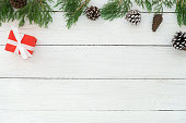 istock Christmas frame made of fir leaves, pine cones and red gift box with decoration rustic elements on white wooden 1046397024