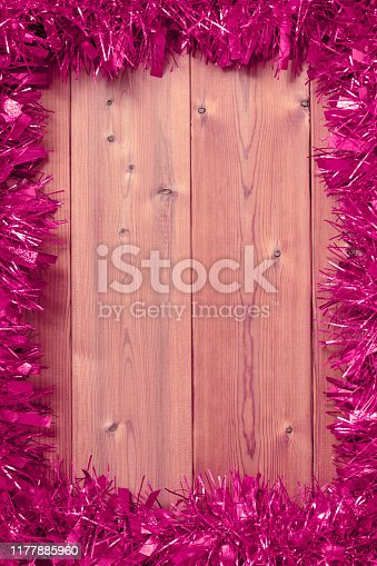 Frame made of Christmas holiday garland on a wooden background. Space for copy.