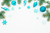 istock Christmas frame made of winter trees, blue decoration and snowflake on white background. Holiday frame. Flat lay, top view 884646592