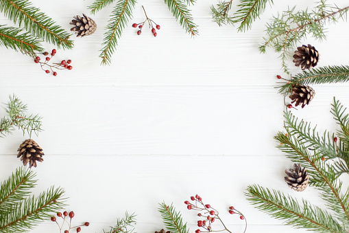 Christmas fir branches, red berries and pine cones frame on white wood, minimalist flat lay. Season's greeting card mock up with space for text. Merry Christmas and Happy Holidays!