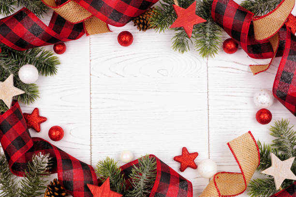 Christmas frame of ornaments, branches, burlap and red and black buffalo plaid ribbon, overhead view on a white wood background stock photo