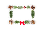 istock Christmas frame of pine cones and fir branches on a white wooden background. Flat lay, top view, copy space 1054919800