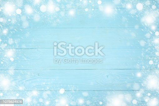 1076063742 istock photo Christmas frame of snowflake with copy space,  on blue board wooden background 1075634926