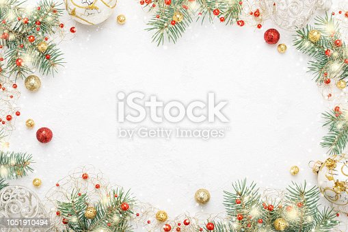 istock Christmas frame of spruce, red & gold christmas decorations on white space. 1051910494