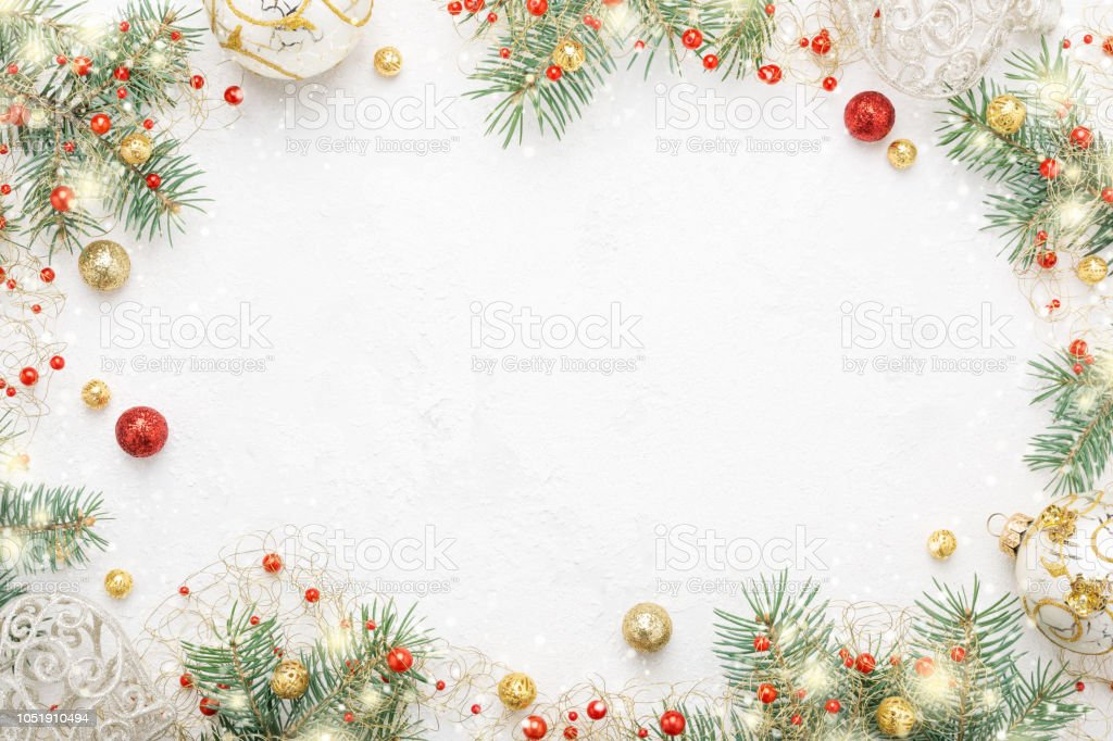 Christmas frame of spruce, red & gold christmas decorations on white space. stock photo