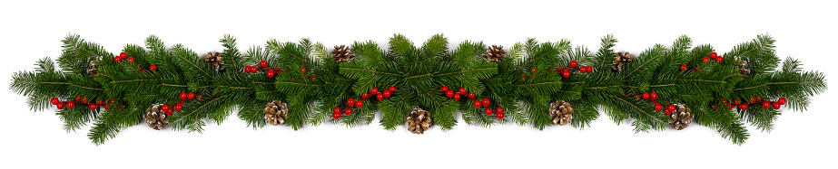 Christmas Border frame of tree branches red berries and pine cones on white background with copy space isolated