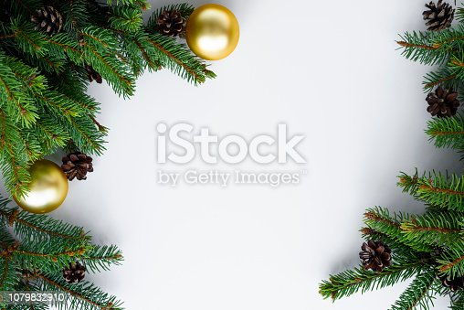 Christmas frame with copy space for happy holidays wishes. Decoration made from evergreen tree branches, cones and gold baubles. Merry Christmas greeting card.