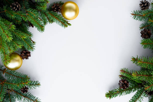 christmas frame with copy space for happy holidays wishes. evergreen tree branches, cones and gold baubles. - happy holidays stock pictures, royalty-free photos & images