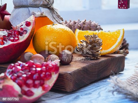 Fresh fruit, nuts and pine cones on window with Christmas decorations. Close-up