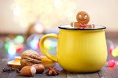 Gingerbread man and yellow mug with Christmas lights.