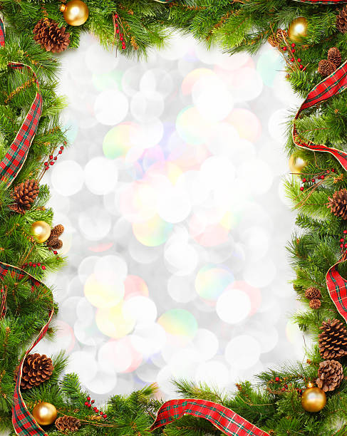 christmas garland frame in front of blurred lights - garland stock photos and pictures