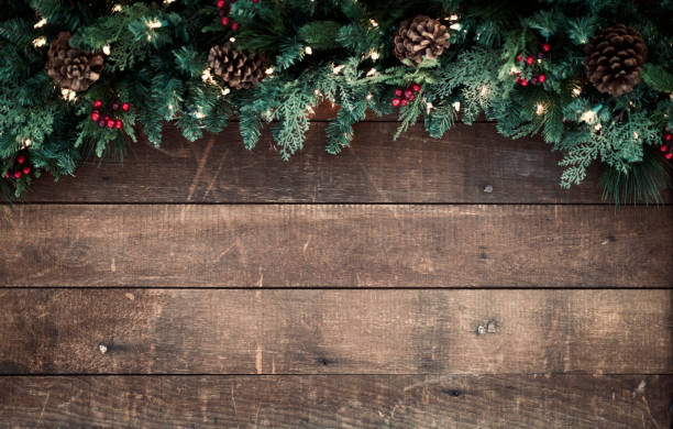 weihnachtsgirlande auf einem alten hölzernen hintergrund - holzdeko weihnachten stock-fotos und bilder