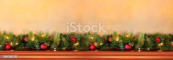 A garland of pine boughs, pine cones, lights, and ornaments rests on top of a mantelpiece beneath a warm toned wall that provides ample room for copy and text.