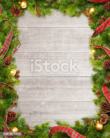 A frame created by a Christmas garland of pine boughs and Christmas ornaments on several wooden whitewashed planks.
