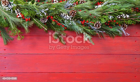 Christmas Garland hung on red barn board background. Copy space
