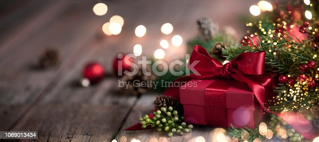 Christmas garland wreath with gift on an old wood background with defocused lights