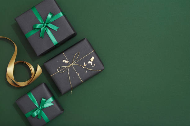 christmas gif flat lay on green background - christmas green stock photos and pictures