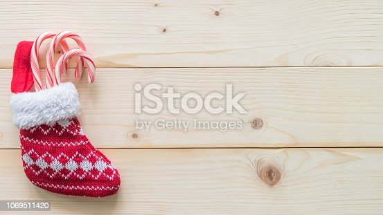 istock Christmas gift background with red baby stocking (sock) candy cane present on white pine wood background for X'mas winter holiday backdrop design decoration 1069511420