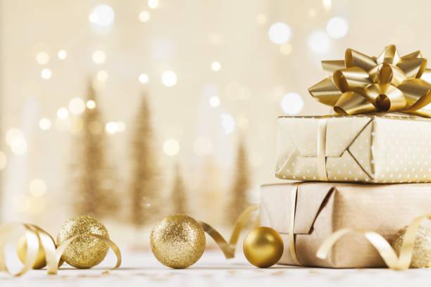 confezione regalo di natale su sfondo bokeh dorato. biglietto d'auguri per le vacanze. - regalo natale foto e immagini stock