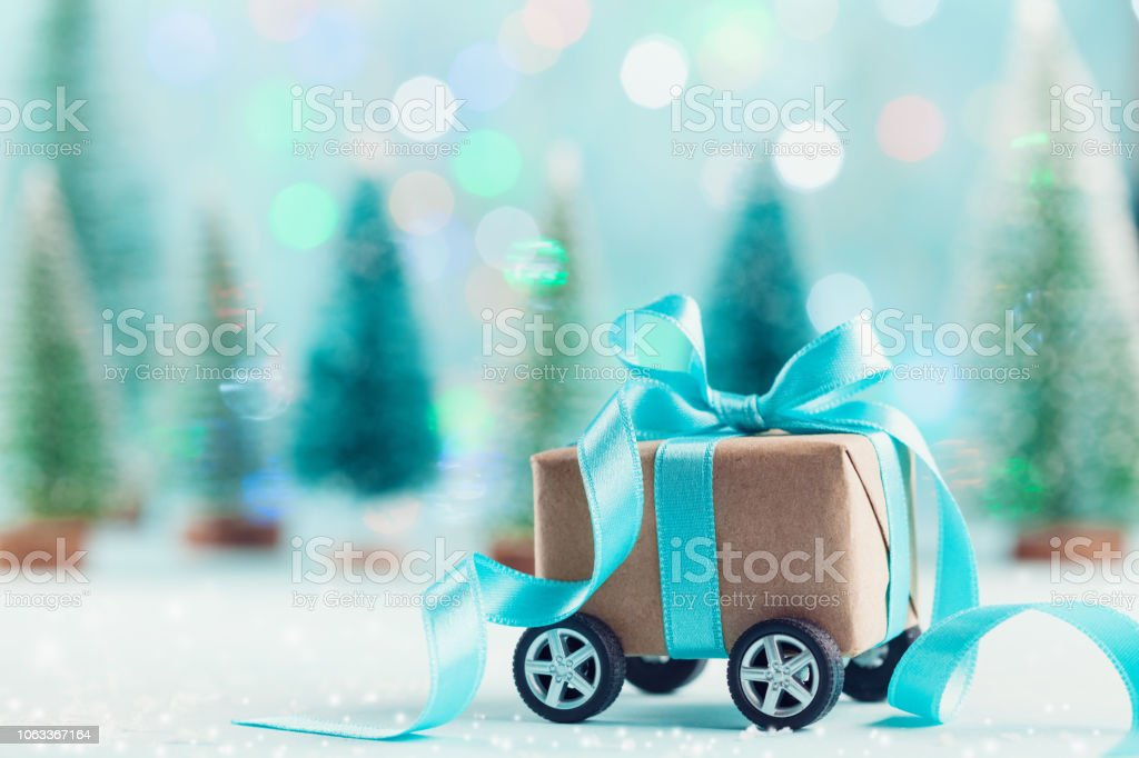 Christmas gift box on wheels against turquoise bokeh background....