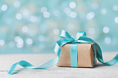 Christmas gift box against turquoise bokeh background. Holiday concept.