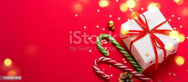 istock Christmas gift box and candy cane with shining lights. Long banner format 1058391848
