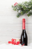 Christmas gift box, champagne bottle and xmas fir tree branch. View with space for your greetings