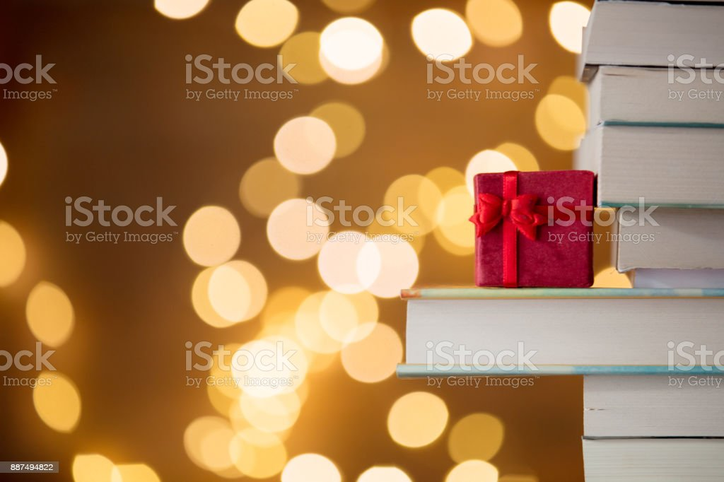 Christmas gift box and pile of books with fairy lights stock photo
