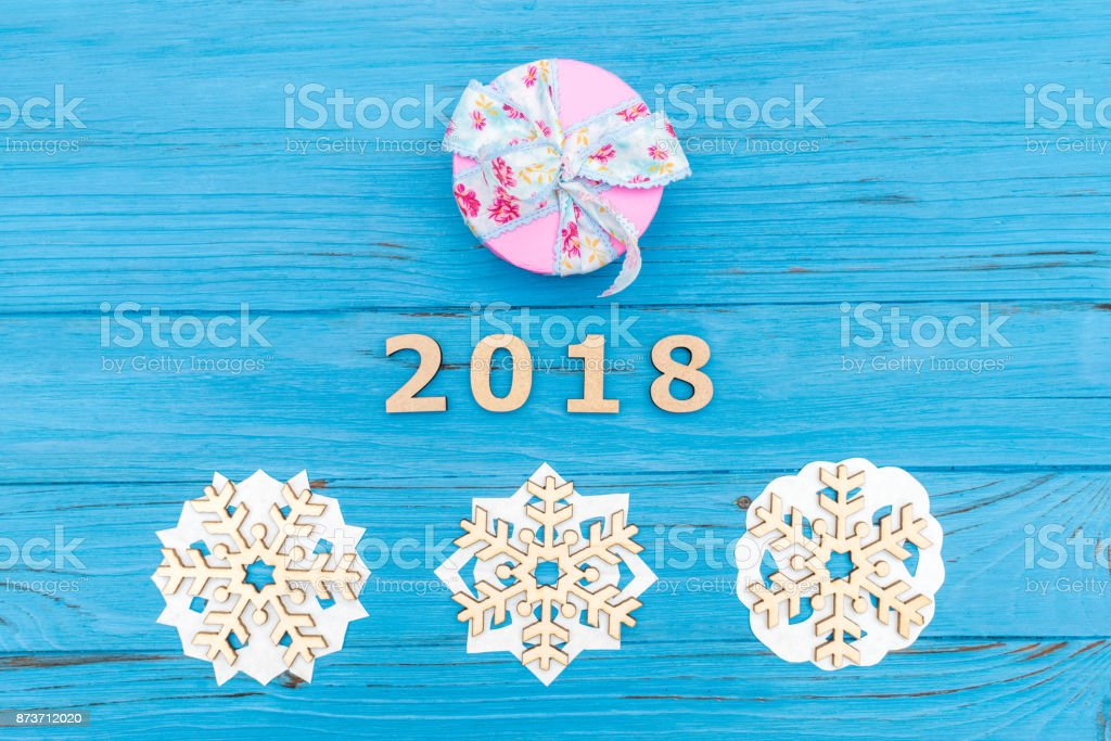 Christmas gift box and thenumbers 2018 and three wooden snowflakes on blue wooden old table stock photo