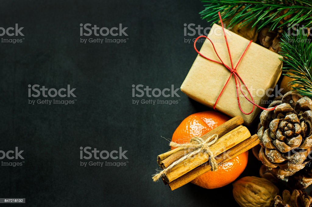 Christmas Gift Box in Craft Paper Tangerine Cinnamon Sticks Fir Tree Branches Pine Cones Walnuts on Black Background Greeting Card Poster Copy Space Top View Flat Lay stock photo