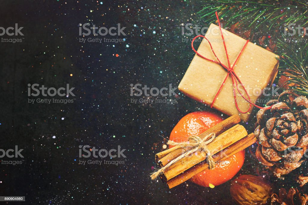 Christmas Gift Box in Craft Paper Tangerine Cinnamon Sticks Fir Tree Branches Pine Cones Walnuts on Black Background Glittering Sparkling Lights Greeting Card Poster Copy Space stock photo