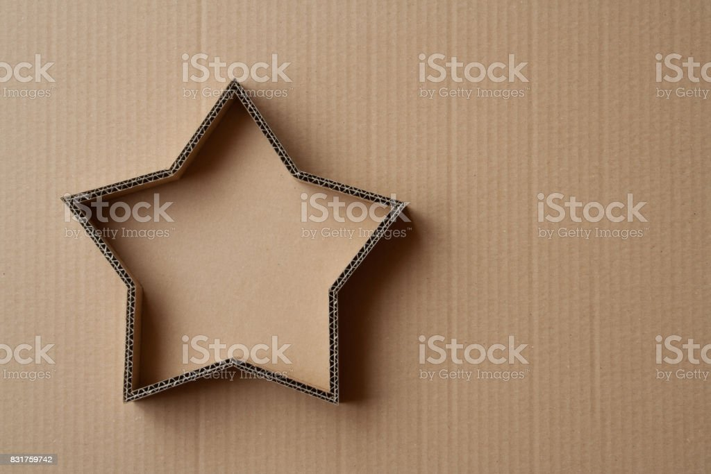 Christmas gift box in the shape of a star on a cardboard background stock photo